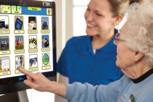 Senior Woman Using a Touchscreen TV with a Caregiver