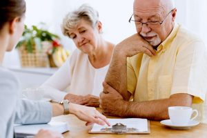 Senior Couple Looking at Clip Board and Speaking With Tax Professional
