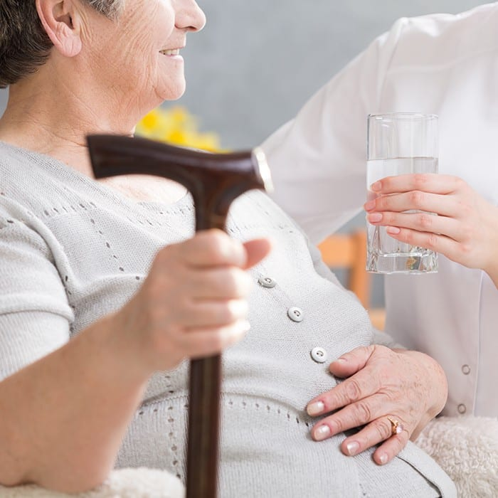 Elderly disabled woman with a walking stick and care giver handing her a glass of water