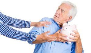 Senior Man Holding Piggy Bank Away From Reaching Hands