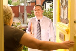 Man in Shirt and Tie Speaking with Senior Woman Standing at Front Door
