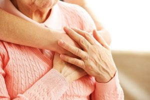 Hands Held Over Senior Woman's Heart