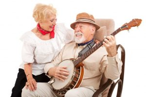 Senior Man Playing Banjo While Smiling Senior Woman Listens