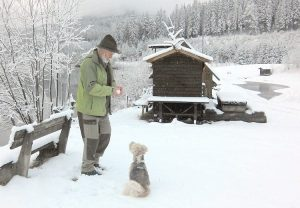 Senior Man and Dog Playing in the Snow