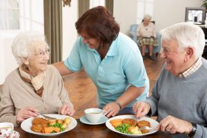 Senior Couple Eating and Speaking with a Care Professional