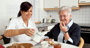 Senior Eating Breakfast While Woman Pours Cream in Coffee