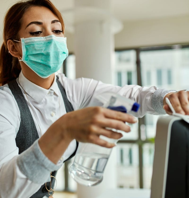 Woman With Mask Disinfecting