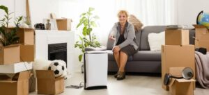 Woman Sitting On Couch Surrounded by Packing Boxes