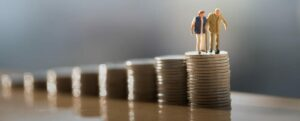 Figurines of a Senior Couple Standing on a Stack of Quarters